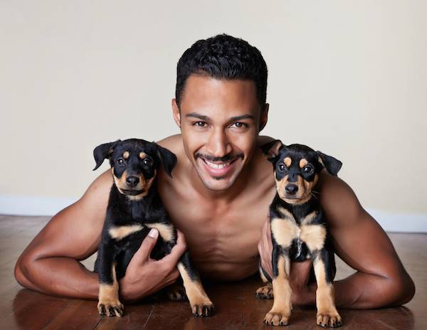 Shirtless Man With Two Puppies