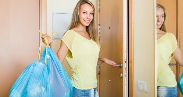 Smiling Housewife With Bags Of Household Garbage Indoor